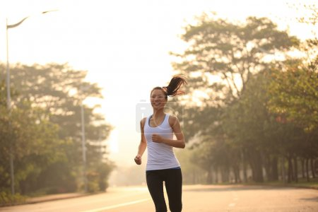 Young fitness woman runner running outdoor