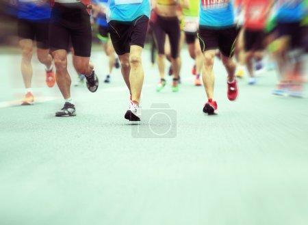 Unidentified marathon athletes legs running on city road