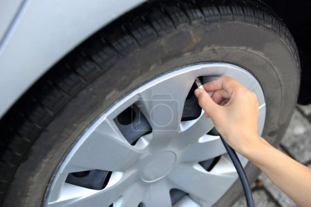 Checking add air pressure . pumping air into auto wheel. vehicle safe concept.