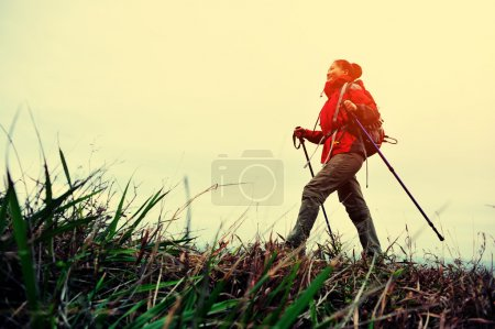 Woman hiker hiking on seaside mountain trail