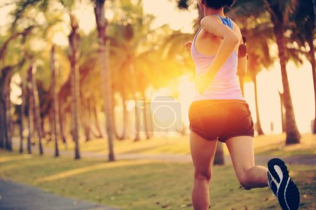 Photo for Runner athlete running at tropical park. woman fitness jogging workout wellness concept. - Royalty Free Image