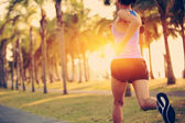 Runner athlete running at tropical park. woman fitness jogging workout wellness concept.