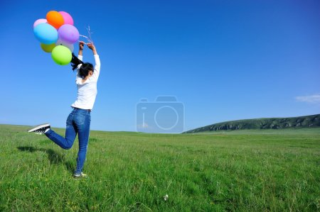 Woman running with colored balloons