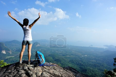 Woman with open arms over sky