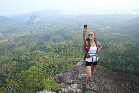 Photo pour Randonneuse avec smartphone prenant selfie sur le sommet de la montagne - image libre de droit