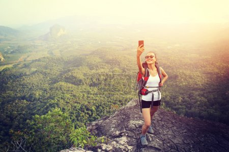 Hiker on mountain top with smartphone