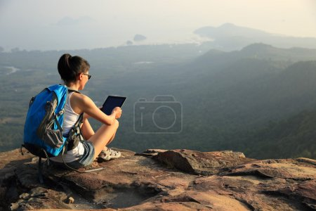 Hiker on mountain top with tablet pc