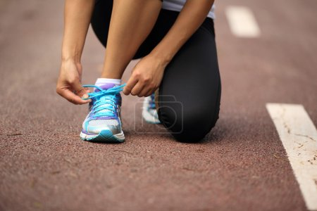 Female runner tying shoelaces