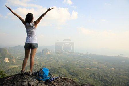 Photo for Cheering woman hiker with open arms at mountain top - Royalty Free Image