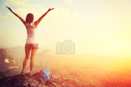 Cheering woman at mountain top