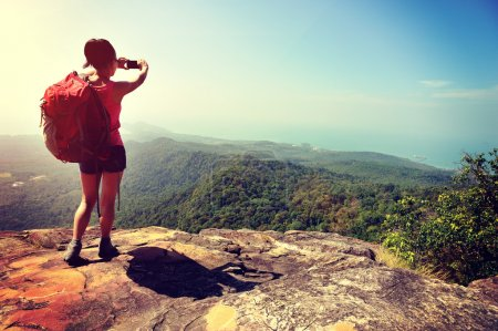 Woman tourist taking picture mountain top