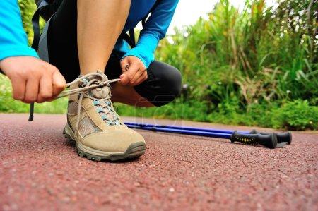 Woman hiker tying shoelace