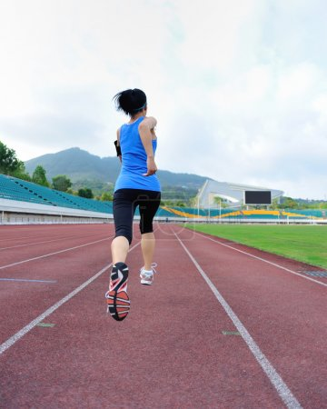 Photo for Young fitness woman running on stadion track - Royalty Free Image