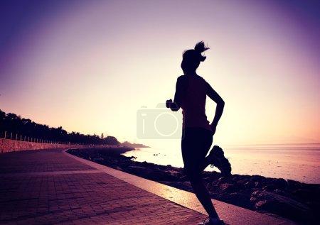 Female athlete running at seaside