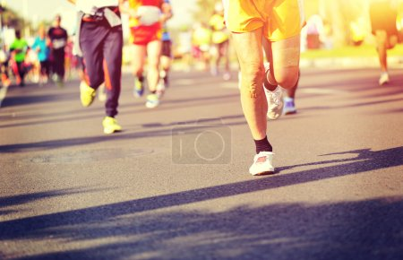 Marathon athletes legs running on road
