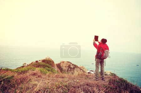 Photo for Woman hiker taking photo with digital tablet on seaside trail - Royalty Free Image