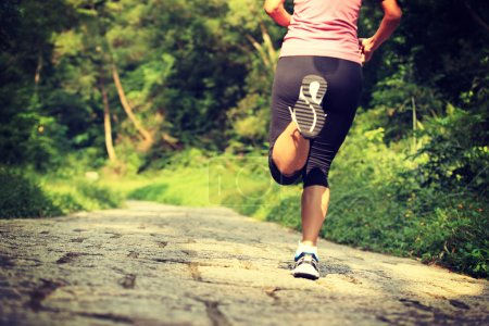 Female athlete running in forest