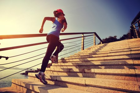Photo for Healthy lifestyle sporty woman running up on stone stairs over seaside - Royalty Free Image