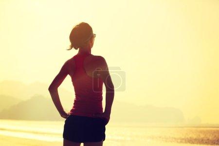 Photo pour Jeune femme de fitness relaxant au lever du soleil bord de mer - image libre de droit