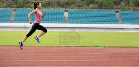 Photo for Young fitness woman runner running on track - Royalty Free Image