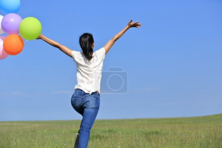 Woman running and jumping with balloons