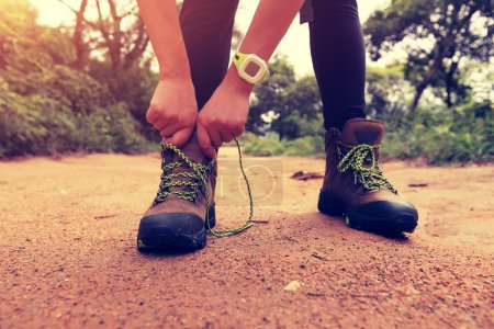 female hiking tying shoelace