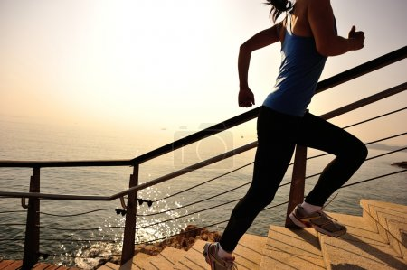 Photo for Healthy lifestyle sports woman running up on stone stairs sunrise seaside - Royalty Free Image