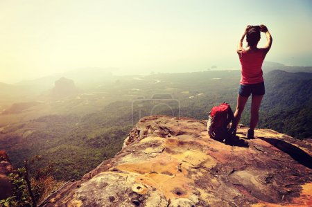 Photo for Woman hiker taking photo with digital camera at mountain peak cliff - Royalty Free Image