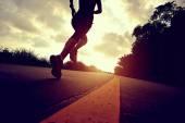 Sportovec běžec běží na pobřežní silnici