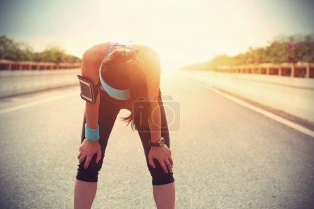Photo for Tired woman runner taking rest after running hard on city road - Royalty Free Image