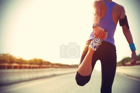 Photo for Young fitness woman stretching legs before running - Royalty Free Image