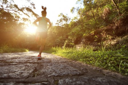 Runner athlete running on forest trail. woman fitn...