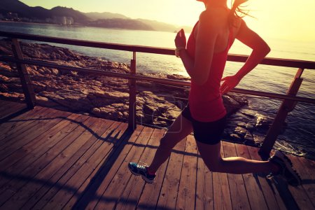 Photo for Young fitness woman legs running on seaside wooden boardwalk - Royalty Free Image