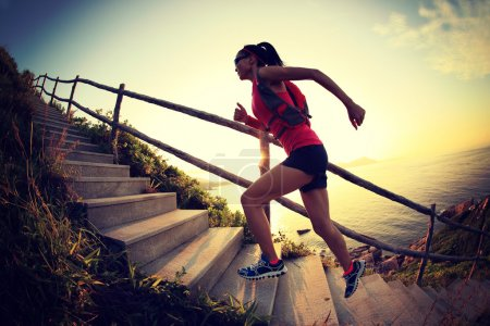 Photo for Fitness woman running up stairs over natural background - Royalty Free Image
