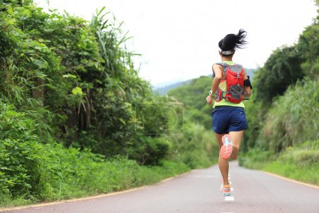 female athlete running on forest trail
