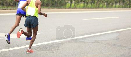 Photo pour Coureurs de marathon en cours d'exécution sur la route de la ville - image libre de droit