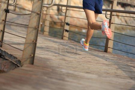 female legs running on boardwalk