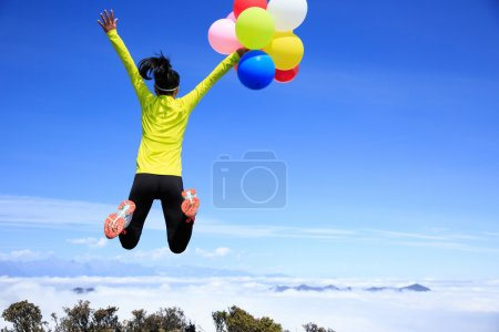 Cheering young woman colorful balloons