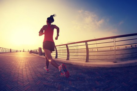 Photo for Young fitness woman running at seaside - Royalty Free Image