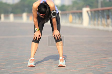 Photo for Tired woman runner taking rest after running hard on sunshine seaside - Royalty Free Image