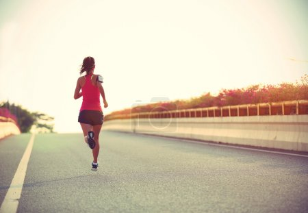 woman runner running on road