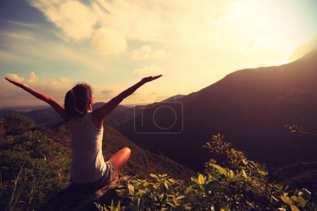 Photo for Woman practicing yoga on mountain peak - Royalty Free Image