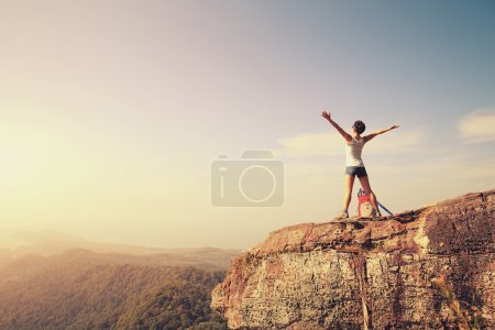 Photo for Cheering woman hiker with open arms at mountain peak - Royalty Free Image