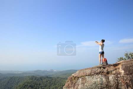 young woman with camera on mountain