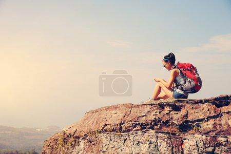 woman using smartphone  on mountain peak