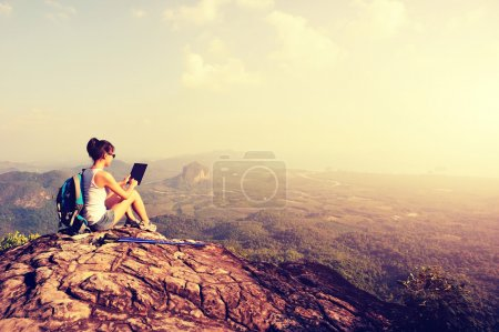 woman using digital tablet on mountain