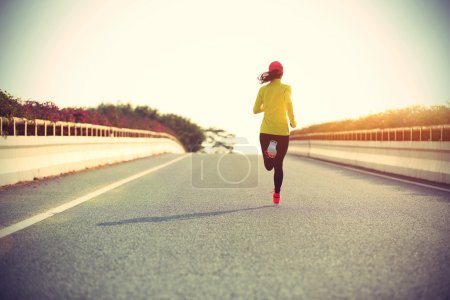 sporty woman runner on road