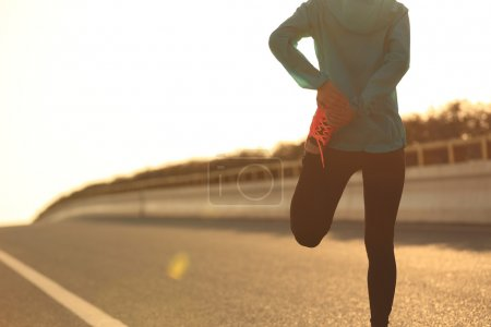 fitness woman runner stretching leg