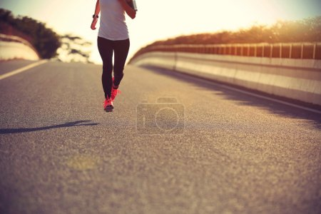sporty woman running on road