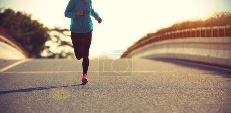 Photo for Young fitness woman runner running on sunrise road - Royalty Free Image
